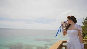 一个使目炫的新娘享受从俯视海洋和礁石的阳台的高度的幸福 爱飞行  异乎寻常 库存照片
