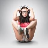 一个侈奢的姿势的女孩与耳机 免版税库存照片