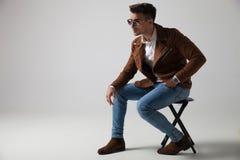 一个供以座位的时装模特儿佩带的太阳镜的侧视图 免版税库存图片