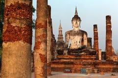 一个供以座位的菩萨雕象的看法在被破坏的专栏中的在Wat Mahathat,古老佛教寺庙在Sukhothai历史公园 图库摄影