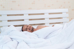 一个俊男在床上睡觉无辜地在工作前 免版税库存图片