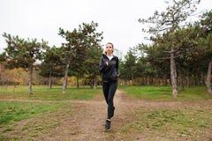 一个俏丽的健身女孩的画象耳机跑的 免版税库存图片
