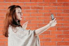 一个俏丽的女孩做与智能手机的selfie,送空气亲吻 库存照片