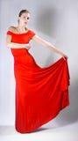 一个俏丽的女孩在一件红色礼服穿戴了 免版税图库摄影