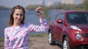 一个俏丽的女孩在汽车前面站立,投掷钥匙,捉住并且挥动他们在框架 r 影视素材