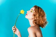 一个俏丽的女孩的画象有一朵黄色花的 免版税库存照片