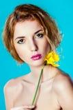 一个俏丽的女孩的画象有一朵黄色花的 库存照片