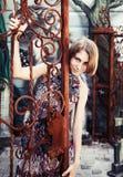 一个俏丽的女孩的画象生锈的门的 免版税库存照片