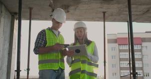 一个修造的建设中人的监督员谈论与工程师设计师妇女建筑进展和 股票视频