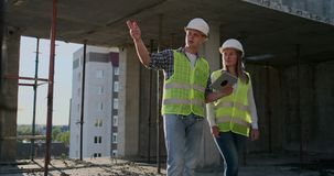 一个修造的建设中人的监督员谈论与工程师设计师妇女建筑进展和 股票录像