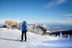 一个倾斜的女子滑雪者在冬天山 免版税库存图片