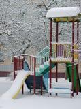 一个偏僻的摇摆集合,操场,在雪下的冬天,在城市围场 免版税图库摄影