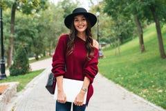 一个偶然微笑的亚裔女孩的画象在帽子穿戴了 免版税库存照片
