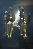 一个充满烟雾的大厦的消防队员 库存照片