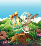 一个兔宝宝和一个大复活节彩蛋在树桩上 库存图片