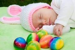 一个兔宝宝帽子的婴孩用复活节彩蛋 免版税库存图片