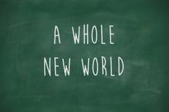 一个全新的世界手写在黑板 免版税库存照片