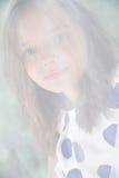 一个八岁的女孩的画象在滤网薄纱后的 库存图片