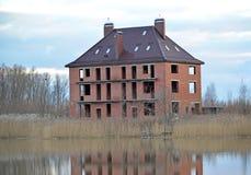 一个公寓村庄的建筑在湖的银行的 免版税库存照片