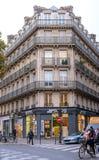 一个公寓的门面有一个阳台的在巴黎交叉路的秋天树中  免版税库存照片