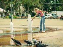 从一个公开喷泉的鸽子饮用水在招待附近女孩 图库摄影