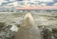 一个具体码头的透视图在海的日落的 免版税库存照片
