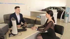 一个典雅的女孩谈话与坐在一张桌上的汽车推销员在陈列室里 股票视频