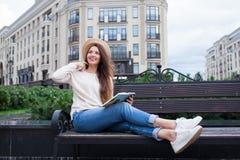 一个典雅的帽子的一名年轻美丽的妇女坐一条长凳在一个新的住宅邻里并且读一个法院记录 她翻转thro 免版税图库摄影
