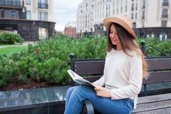 一个典雅的帽子的一名年轻美丽的妇女坐一条长凳在一个新的住宅邻里并且读一个法院记录 她翻转thro 库存照片