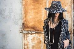 一个典雅的豹子衣物和帽子的可爱的妇女 免版税库存照片