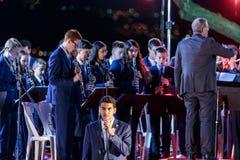一个军乐队陪同的歌手执行以色列Atikva的专题歌在纪念仪式在纪念站点对Th 图库摄影