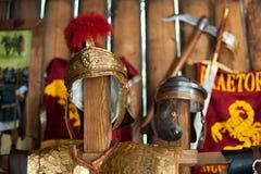 一个军团的战士的古老罗马盔甲的复制品以武器仓库的日志墙壁的为背景 免版税库存图片