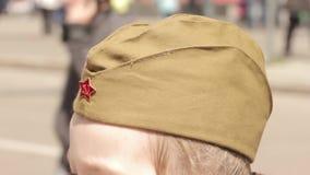 一个军用盖帽的女孩在被弄脏的背景的一条拥挤的街上 股票录像