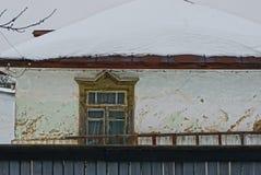 一个农村在屋顶的房子和雪的门面有窗口的在篱芭后 免版税图库摄影