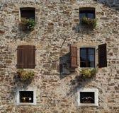 一个农村房子的门面有花的在每个窗口里 免版税库存照片
