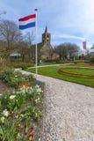 一个农村教会的看法在荷兰村庄在早期的春天,在那里庭院是几朵花和突出地荷兰旗子, 免版税库存图片