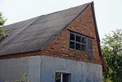 一个农村砖房子的片段有顶楼和窗口的 库存照片