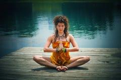 一个冥想的瑜伽位置的妇女由湖 免版税图库摄影