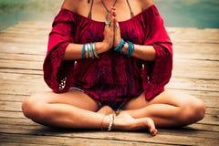 一个冥想的瑜伽位置的妇女由湖 免版税库存照片