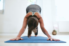 一个冥想的瑜伽姿势的适合的妇女在健身房 免版税库存照片