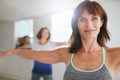 一个冥想的瑜伽姿势的适合的妇女在健身房 免版税库存图片