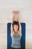 一个冥想的瑜伽姿势的适合的妇女在健身房 库存图片