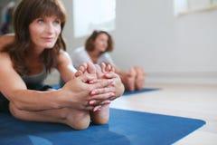 一个冥想的瑜伽姿势的适合的妇女在健身房 图库摄影