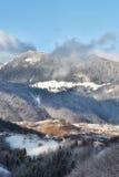一个冬天的晴天,在与Bucegi山的狂放的特兰西瓦尼亚小山在背景中 免版税库存照片