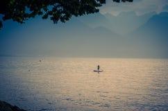 一个冲浪板的人有在湖Leman,瑞士的桨的 库存图片