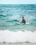 一个冲浪的女孩在正确的波浪等待在海洋 库存图片