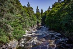 一个冲的小河、森林和小村庄的看法在Invermoriston 图库摄影