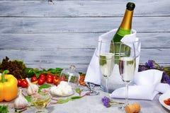 一个凉快的香槟瓶和hampagne玻璃的特写镜头在新鲜食品产品旁边在灰色木背景 免版税图库摄影