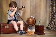 一个减速火箭的内部和一个老电话的一个孩子坐地板 库存照片