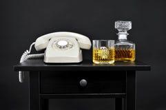 一个减速火箭的电话、一个瓶和一块玻璃与酒在桌上, 免版税库存图片